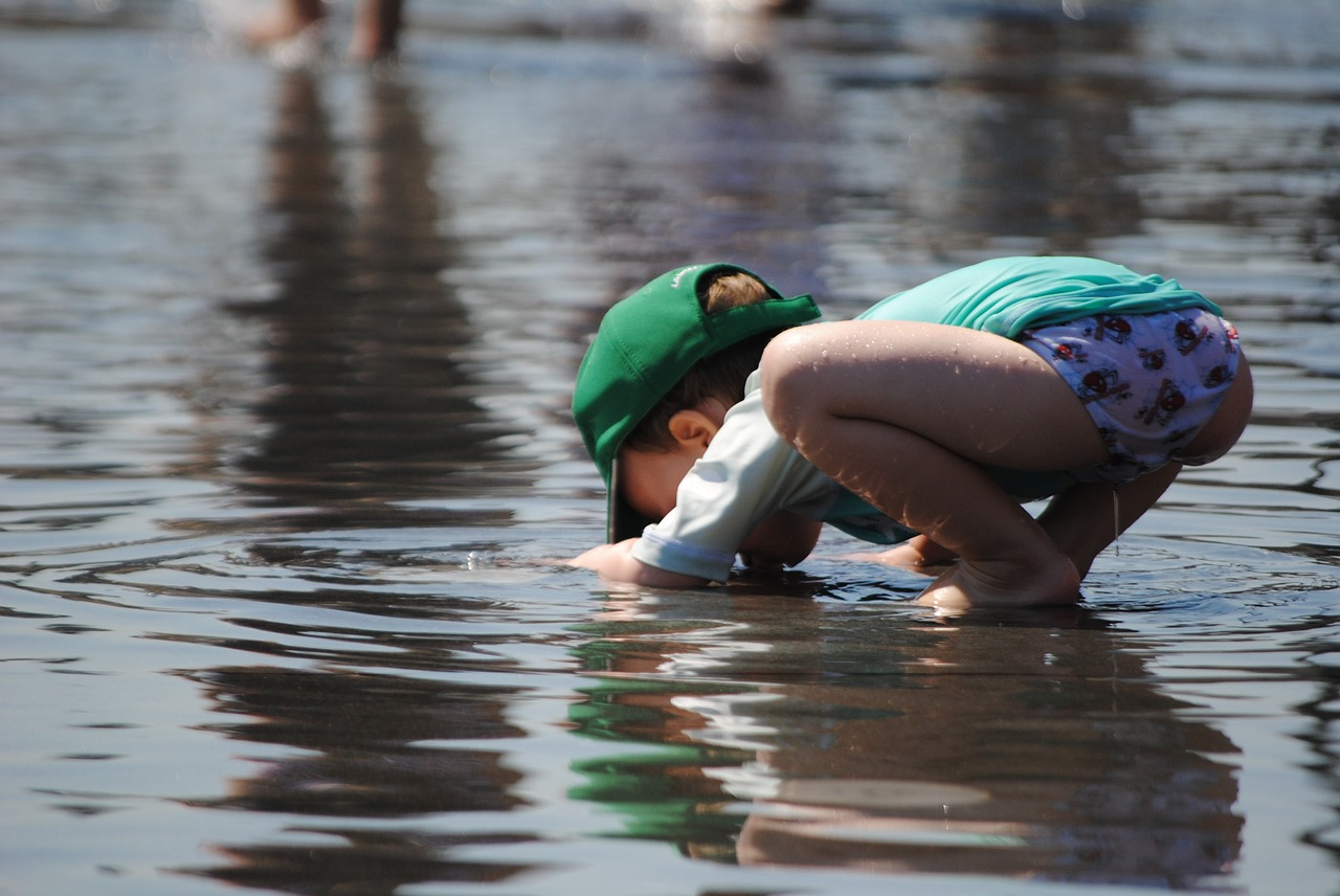 Child Playing In Water Toddler In Summer Child