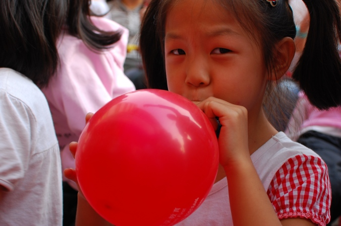 Girl_inflating_a_red_balloon